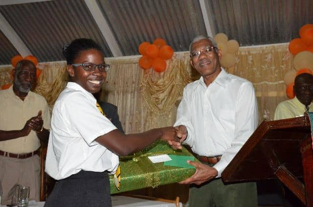 Elisa Hamilton being presented with a laptop computer by President Granger.